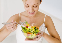 Woman eating bowl of vegetables.